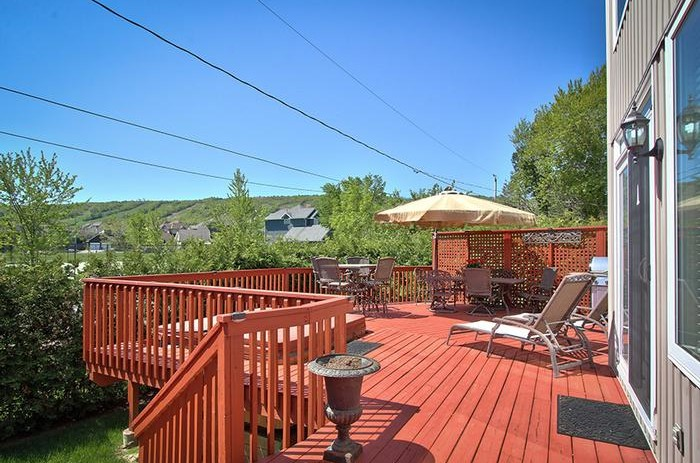 This 106 Birchview chalet from Stay at Blue Mountain features double patio doors that lead to the upper deck with a seating area, hot tub and BBQ with a beautiful view of Blue Mountain