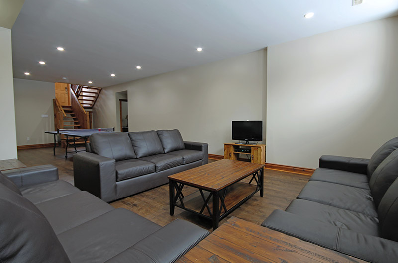 This Stay at Blue Mountain chalet rental comes with leather seating in the lower level of the 109 Plater St location