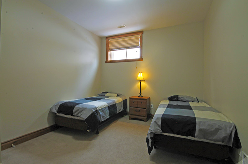 Two twin beds in the lower level of the chalet located at 109 Plater St from Stay at Blue Mountain