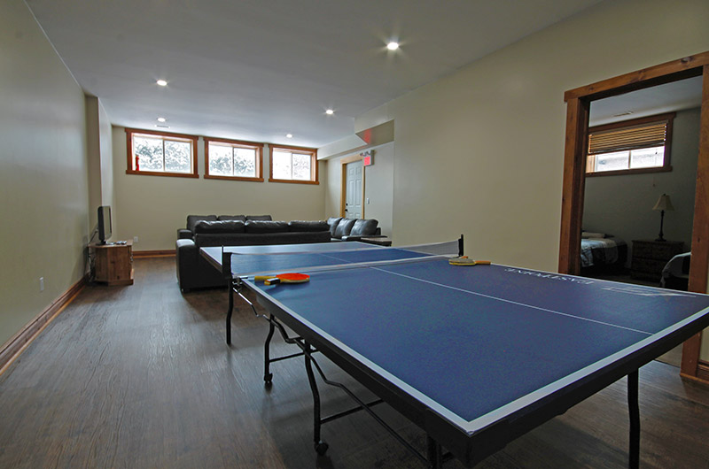 The lower level of 109 Plater St has a huge family room and a ping pong table for your enjoyment at this chalet offered from Stay at Blue Mountain