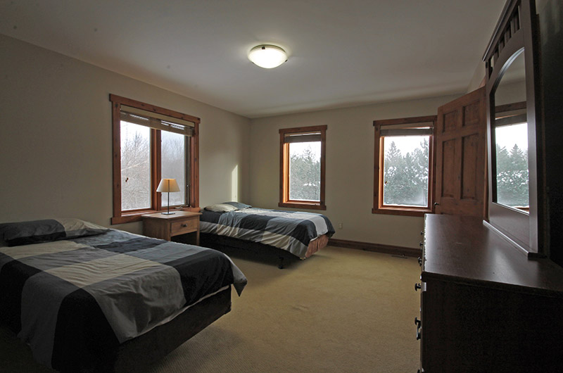 The upper floor bedroom offered from a Stay at Blue Mountain chalet comes with two twin beds at 109 Plater St