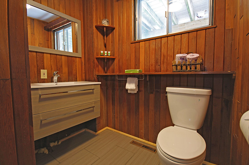 Softwood styled bathroom comes equipped with a toilet, sink, shower & bathtub in this chalet located at 128 Birchview - Offered from Stay at Blue Mountain